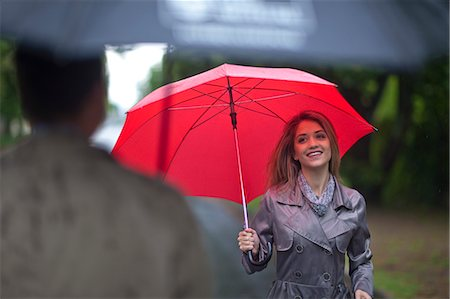 people with umbrellas in the rain - Young woman meeting man in park Stock Photo - Premium Royalty-Free, Code: 649-07520866