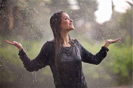 Drenched young woman with arms open in rainy park Stock Photo - Premium Royalty-Free, Code: 649-07520867
