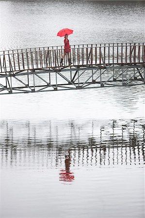 Young woman in red crossing footbridge in rain Stock Photo - Premium Royalty-Free, Code: 649-07520860