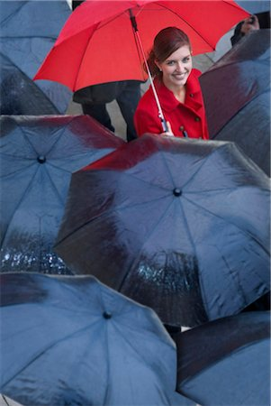 people with umbrellas in the rain - Young woman with red umbrella amongst black umbrella's Stock Photo - Premium Royalty-Free, Code: 649-07520862