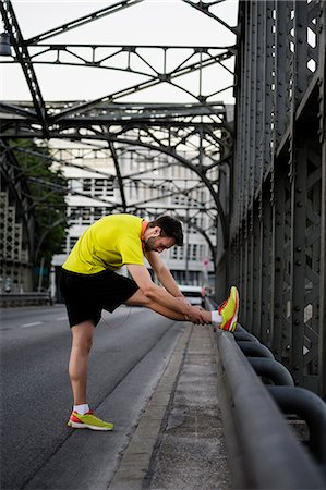 physical fitness - Young male runner stretching legs on bridge Stock Photo - Premium Royalty-Free, Code: 649-07520909