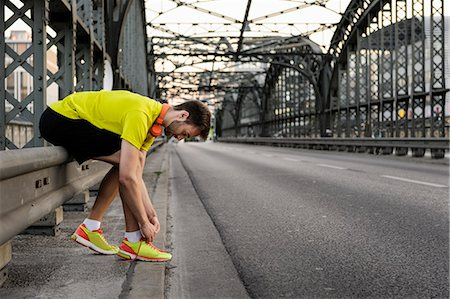 Young male runner tying shoelace on bridge Stock Photo - Premium Royalty-Free, Code: 649-07520914