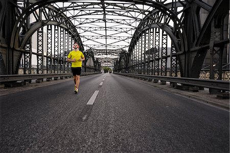 Young male athlete running on bridge Stock Photo - Premium Royalty-Free, Code: 649-07520910