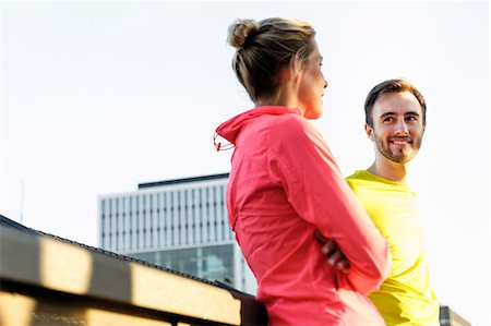 Young male and female runners talking on bridge Stock Photo - Premium Royalty-Free, Code: 649-07520929