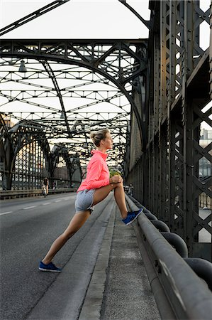 Young female runner stretching legs on bridge Stock Photo - Premium Royalty-Free, Code: 649-07520922