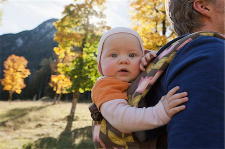 Father carrying baby daughter in carrier Stock Photo - Premium Royalty-Free, Code: 649-07520965