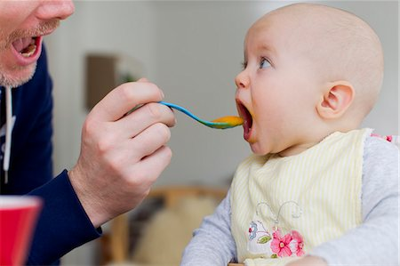 Father spoon feeding baby daughter Stock Photo - Premium Royalty-Free, Code: 649-07520969