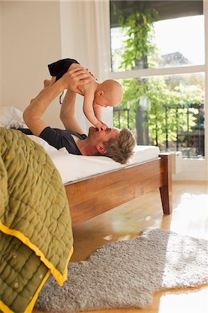 Father lifting baby daughter on bed Stock Photo - Premium Royalty-Free, Code: 649-07520974
