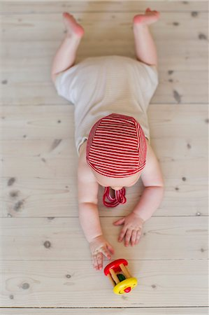 reaching - Baby girl lying on floor with toy Stock Photo - Premium Royalty-Free, Code: 649-07521012