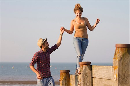 Young woman balancing on groynes holding man's hand Stock Photo - Premium Royalty-Free, Code: 649-07521051