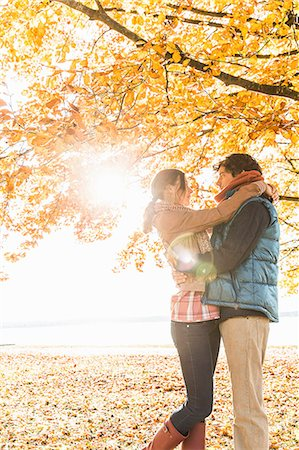 fall trees lake - Couple hugging by tree in sunlight Stock Photo - Premium Royalty-Free, Code: 649-07521111