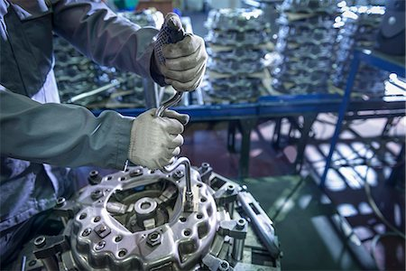 Close up of engineer assembling industrial clutch on production line Stock Photo - Premium Royalty-Free, Code: 649-07521189