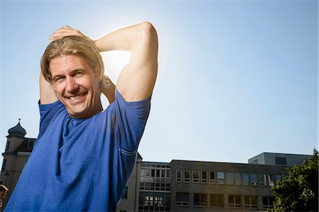 Mid adult man stretching during training on city rooftop Stock Photo - Premium Royalty-Free, Code: 649-07559758