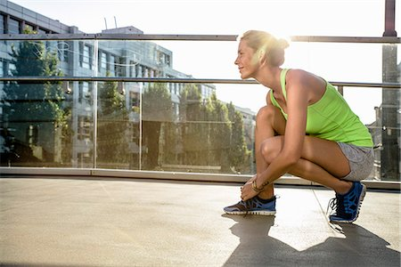 physical fitness - Young female runner tying shoelace on city footbridge Stock Photo - Premium Royalty-Free, Code: 649-07559753