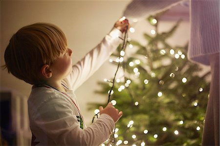 Young boy putting up christmas tree lights Stock Photo - Premium Royalty-Free, Code: 649-07559802