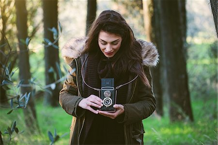 Young woman with camera in the woods Stock Photo - Premium Royalty-Free, Code: 649-07559829