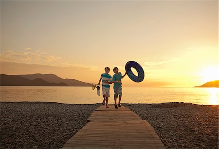 Two brothers running on boardwalk, Fethiye, Turkey Stock Photo - Premium Royalty-Free, Code: 649-07559945