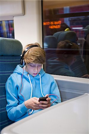Teenage boy in headphones and using smartphone on train Stock Photo - Premium Royalty-Free, Code: 649-07559956