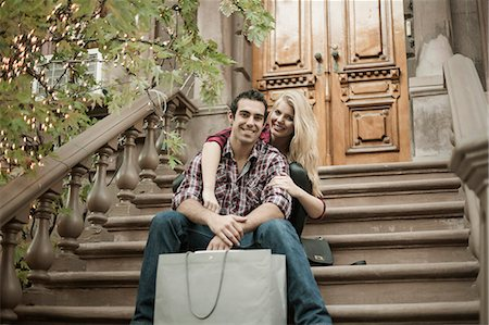 Young couple sitting on traditional city apartment steps Stock Photo - Premium Royalty-Free, Code: 649-07560005