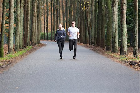 Couple running through forest Stock Photo - Premium Royalty-Free, Code: 649-07560007
