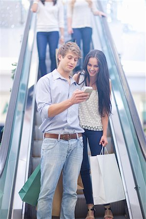 shopping mall - Young couple using cellular phone on escalator Stock Photo - Premium Royalty-Free, Code: 649-07560057