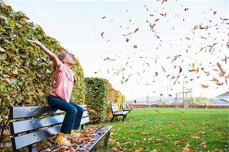 Boy sitting scattering leaves into air Stock Photo - Premium Royalty-Free, Code: 649-07560051