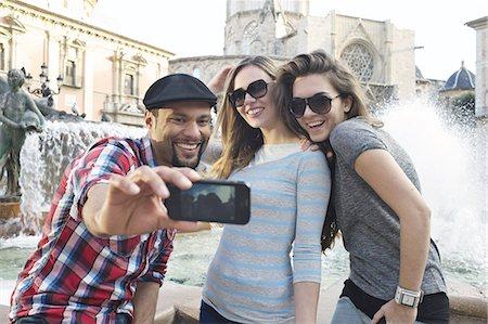 Tourist friends taking self portrait, Plaza de la Virgen, Valencia, Spain Stock Photo - Premium Royalty-Free, Code: 649-07560087
