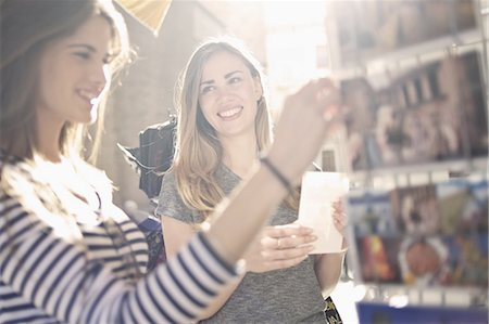 Two young female friends looking at postcards, Valencia, Spain Stock Photo - Premium Royalty-Free, Code: 649-07560094