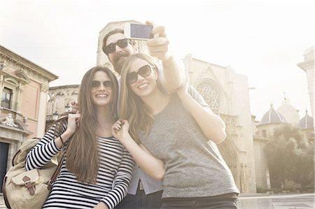 Three tourists taking self portrait, Plaza de la Virgen, Valencia, Spain Stock Photo - Premium Royalty-Free, Code: 649-07560095