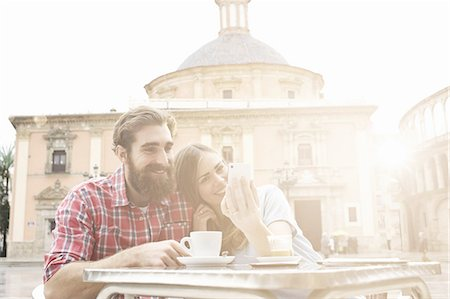 people and vacation - Young couple having coffee in sidewalk cafe, Plaza de la Virgen, Valencia, Spain Stock Photo - Premium Royalty-Free, Code: 649-07560108