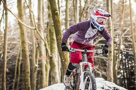 Young female mountain biker riding through forest Stock Photo - Premium Royalty-Free, Code: 649-07560119