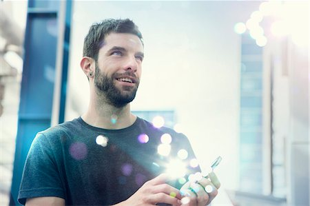 futuristic - Mid adult man looking up at lights coming from smartphone Stock Photo - Premium Royalty-Free, Code: 649-07560127
