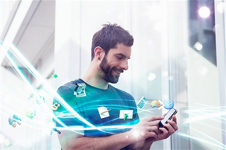 streaming - Mid adult man with apps and lights coming from smartphone Stock Photo - Premium Royalty-Free, Code: 649-07560128