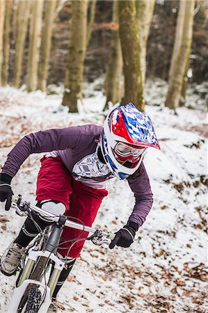 Young female mountain biker riding downhill through forest Stock Photo - Premium Royalty-Free, Code: 649-07560123