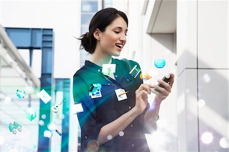 futuristic - Young businesswoman holding smartphone with apps and icons coming out of it Stock Photo - Premium Royalty-Free, Code: 649-07560134