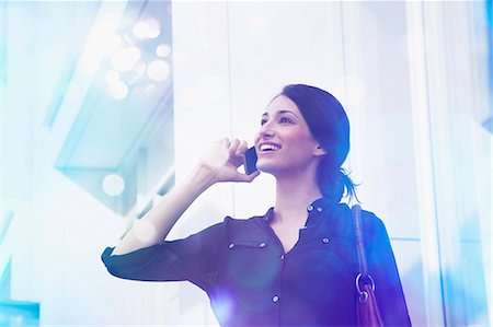 Young businesswoman talking on smartphone with lights coming out of it Stock Photo - Premium Royalty-Free, Code: 649-07560135