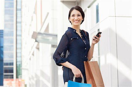 purchase - Young businesswoman carrying smartphone and shopping bags Stock Photo - Premium Royalty-Free, Code: 649-07560136