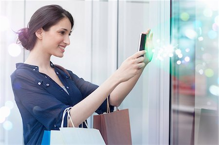 Young businesswoman looking at smartphone with lights coming out of it Stock Photo - Premium Royalty-Free, Code: 649-07560137