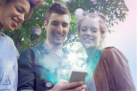 streaming - Three friends looking at smartphone with lights coming out of it Stock Photo - Premium Royalty-Free, Code: 649-07560139