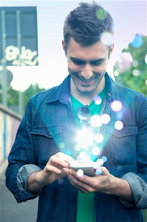 futuristic - Young man texting on smartphone with glowing lights coming out of it Stock Photo - Premium Royalty-Free, Code: 649-07560148