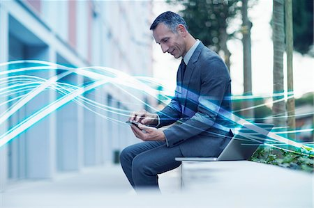 streaming - Waves of blue light and businessman texting on smartphone Stock Photo - Premium Royalty-Free, Code: 649-07560155