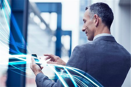 streaming - Waves of blue light and businessman using touchscreen on smartphone Stock Photo - Premium Royalty-Free, Code: 649-07560158