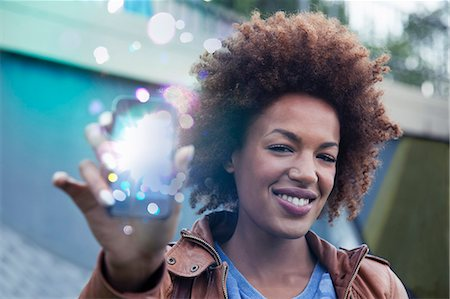 streaming - Young woman holding up smartphone with glowing lights coming out Stock Photo - Premium Royalty-Free, Code: 649-07560151
