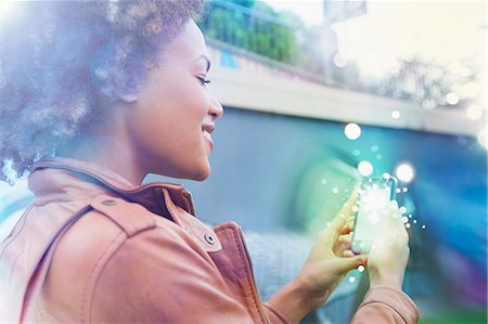 streaming - Young woman looking at smartphone with glowing lights coming out Stock Photo - Premium Royalty-Free, Code: 649-07560153