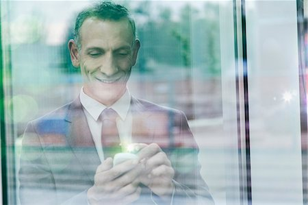 Businessman with glowing finger using smartphone touchscreen Stock Photo - Premium Royalty-Free, Code: 649-07560169