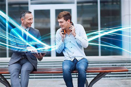 people sitting on bench - Businessman and young man watching digital tablet and waves of blue light Stock Photo - Premium Royalty-Free, Code: 649-07560161
