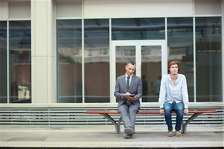 people sitting on bench - Businessman and young man sitting on train station bench Stock Photo - Premium Royalty-Free, Code: 649-07560162