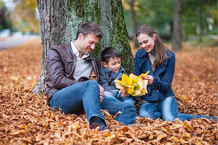 Young boy and parents sitting in park with autumn leaves Stock Photo - Premium Royalty-Free, Code: 649-07560177