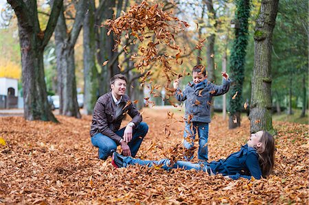 Young boy and parents throwing up autumn leaves in park Stock Photo - Premium Royalty-Free, Code: 649-07560171