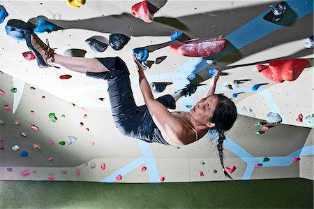 reaching - Mature woman bouldering upside down on climbing wall Stock Photo - Premium Royalty-Free, Code: 649-07560199